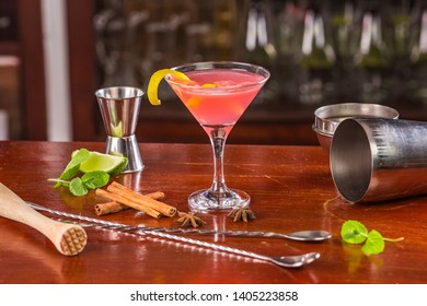 Cosmopolitan cocktail, decorated with lemon zest in a glass on a bar counter surrounded by spices, mint leaves, bar equipment: measuring cup, shaker, bar spoon, masher