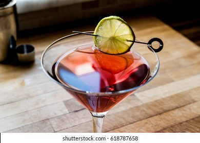 Cosmopolitan Cocktail with shaker on wooden surface.