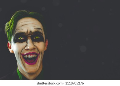Cosplay of a cult character from comics. Joker laughs in the dark. Halloween holidays. Copy space for text