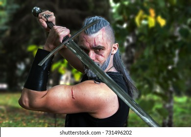 Cosplay, dressed like a hero Geralt of Rivia from the game The Witcher, a fantastic warrior with a sword in his hands