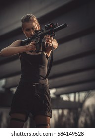 Cosplayer  girl with machine gun in her hands in costume Croft. Cosplay.