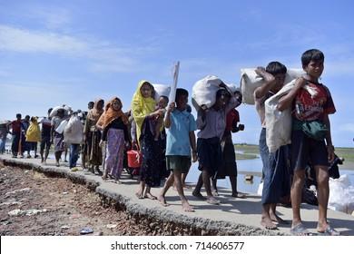 COS'S BAZER, BANGLADESH - SEPTEMBER 11, 2017 Members of Myanmar's Muslim Rohingya minority walk through a broken road at Shah Porir Deep, at Teknaf in Cox's Bazer, Bangladesh on September11, 2017.