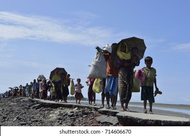 COS'S BAZER, BANGLADESH - SEPTEMBER 11, 2017 Members of Myanmar's Muslim Rohingya minority walk through a broken road at Shah Porir Deep, at Teknaf in Cox's Bazer, Bangladesh on September11, 2017.