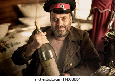 Cossack in a peaked cap and overcoat sits in a hut with a huge bottle of moonshine
