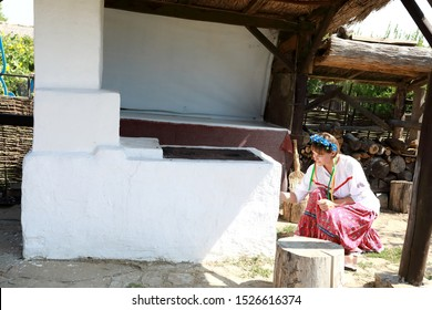 Cossack woman lights fire in russian stove in backyard
