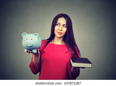 Cost of college education. Perplexed thoughtful woman balancing piggy bank in one hand and book in another.