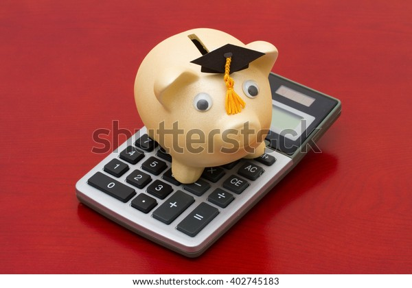 Cost of education, A golden piggy bank with grad cap and calculator on a wood background