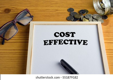 COST EFFECTIVE Business concept - Office desk with White board, glasses, pen, and coins