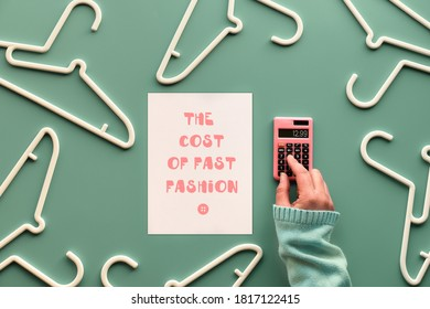 The cost of fast fashion. White plastic hangers, hand with calculator and paper with text. Creative flat lay on pastel green mint background.