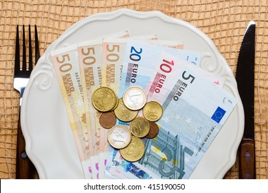 Cost of living, price of food and eating wealth concept. Euro money on kitchen table, plate with cutlery