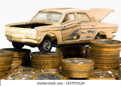 The cost of maintaining an old car. A model of an old car is standing on coins. The concept of expensive maintenance of an old car or its disposal