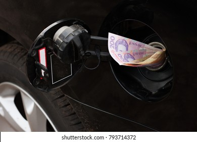 Cost to refueling gasoline. Ukrainian money hryvna stick out in hole for fueling the black car gasoline. Close up
