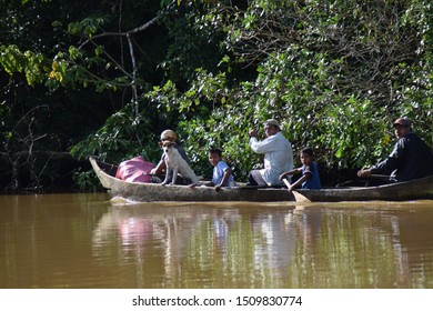 Costa Caribe, Nicaragua, September 24, 2016: Three men, two boys and a dog transporting themselves in a canoe with large trees on the bottom on a sunny day. Colorful photo