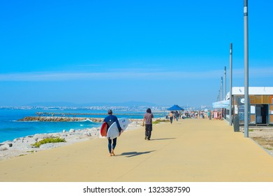 COSTA DA CAPARICA, LISBON, PORTUGAL - SEPTEMBER 17, 2018: People walking by seaside promenade in the sunny summer day. Costa de Caparica is the famous tourist destination