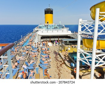COSTA FAVOLOSA, SPAIN - AUGUST 8, 2013: many tourists sunbathing on the deck of cruise liner Costa Favolosa in Mediterranean Sea. The liner was released in 2010 and can carry up to 3020 passengers