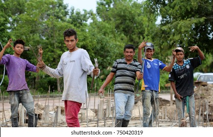 Costa Maya, Mexico, November 2017. Group of happy manual construction workers with tools posing for camera.