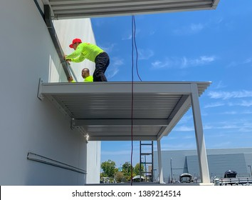 Costa Mesa, Ca  USA - April 25, 2019: Men at work installing a down spout at the rear of a building