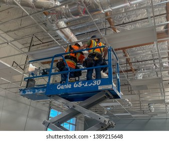 Costa Mesa, Ca  USA - April 25, 2019: Men on a scissor lift installing lighting in a building under construction