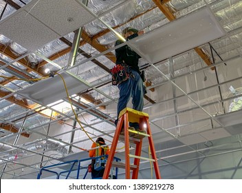 Costa Mesa, Ca  USA - April 25, 2019: Man installing lighting in a drop ceiling on a construction site