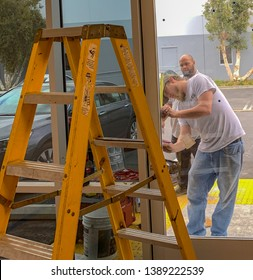 Costa Mesa, Ca  USA - April 25, 2019: en work on installing a door at a construction site