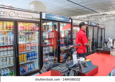 Costa Mesa, California/United States - 07/17/2019: A clerk is ready for customers with several refrigerators full of tall beer cans, located at the Orange County Fair