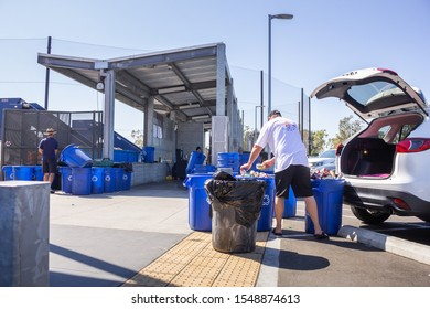 Costa Mesa, California/United States - 09/22/2019: A person places aluminum drinking cans into a blue bin at the OCC Recycling Center.