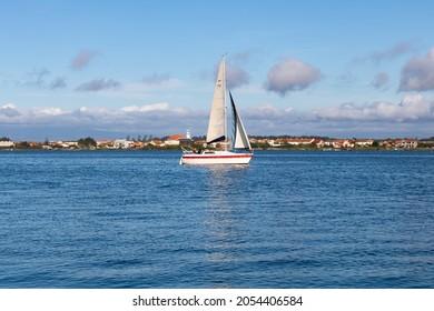 Costa Nova do Prado, Portugal - October 05, 2021: A sailboat known as cutter with a single mast, mainsail and staysail sailing in the blue waters of Ria de Aveiro with view to Gafanha da Encarnação