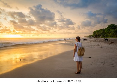 Costa Rica, young girl looking at the ocean at sunset, Playa Carmen.