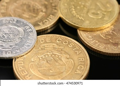 Costa Rican coins close up on black