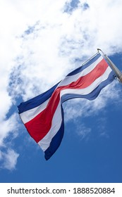 Costa Rican flag in a blue sky with clouds