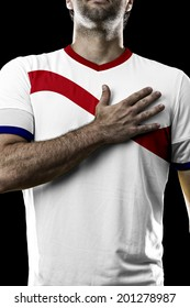 costa rican soccer player, listening to the national anthem with his hand on his chest. On a black background.
