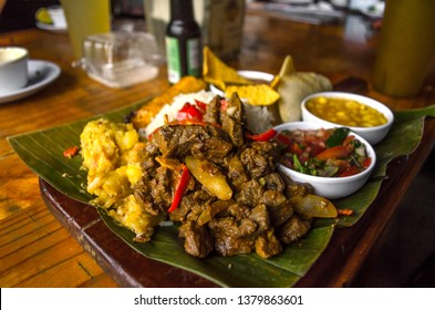 """Costa rican typical food called """"Casado de Res"""". Which is Beef, mashed potatoes, tomato salad, corn soup, rice, fried plantain, beans with nachos and tortillas served over a tamale leaf."""