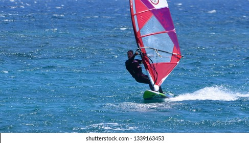 COSTA TEGUISE, LANZAROTE, SPAIN - MARCH 21, 2018: Windsurfer moving at speed on the ocean.