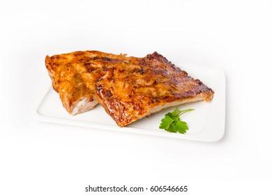Costillar de cerdo asado en una bandeja con perejil
