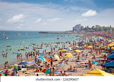 COSTINESTI, ROMANIA - AUGUST 6: Crowded beach with tourists in summer on August 6, 2012 in Costinesti, Romania. Costinesti is a famous summer destination for hundred of thousands of tourists a year.