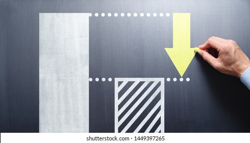 Costs cutting and efficiency concept. Businessman drawing bar graph and arrow on chalkboard.