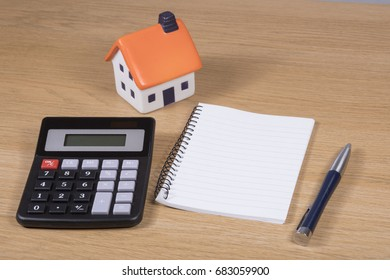 Costs of purchasing your dream house or planning for home improvements concept with a model home, calculator, pen and notebook on a wooden desk