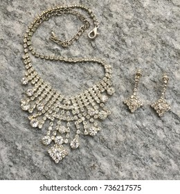 Costume jewelry: necklace and earrings on stone