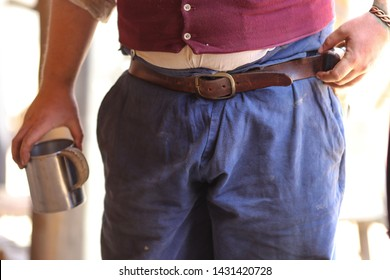 Costumed actors waistline in 1840's American West frontier setting with blue trousers belt and holding a metal coffee cup