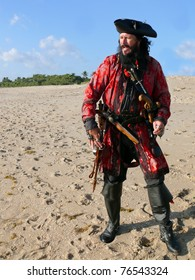 Costumed Pirate on beach.A full length pirate in vintage costume with weapons looks out to sea from the beach.