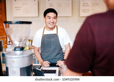 Costumer order Asian barista with smile at coffeeshop.