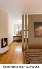 Cosy beige bedroom with fireplace and open dressing room with big mirror