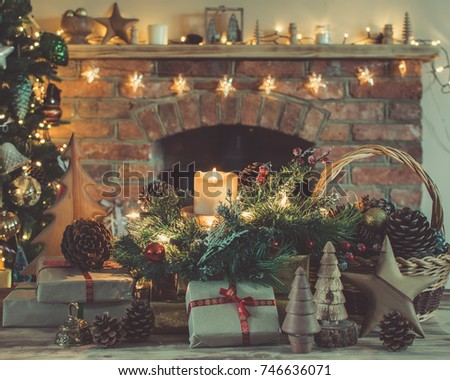 cosy christmas composition presents and decorations on the table in front of the fireplace with