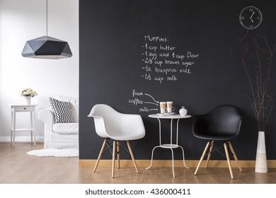 Cosy coffee area in small flat with modern blackboard wall