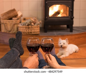 Cosy couple by the fire with red wine and a west highland terrier westie dog.
