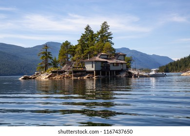 Cosy Home on a private rocky island during a vibrant sunny summer day. Taken in Sechelt Inlet, Sunshine Coast, BC, Canada.