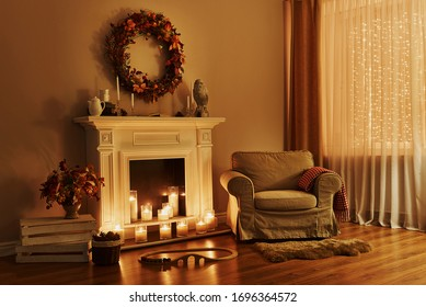 Cosy living room with decor. Cozy fireplace with armchair. Interior in a cozy house