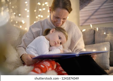 Cosy mother and daughter reading a story at home