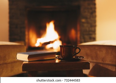 Cosy winter evening in mountain chalet. Cup of hot drink in front of fireplace