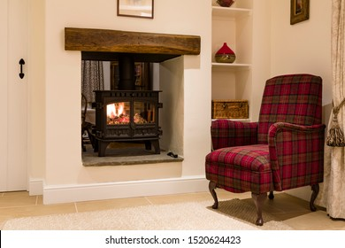 Cosy woodburner and chair in an English home, UK